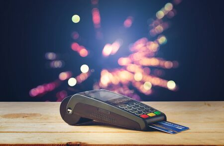 Credit card machine on wood with firework bokeh background