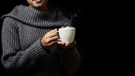 Cup of coffee in the womens hand on dark background