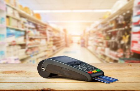 Credit card machine on wood with supermarket background