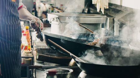 Chefkoch im Wok anbraten. Dramatisches Kochen mit Feuer hart in der Küche Standard-Bild