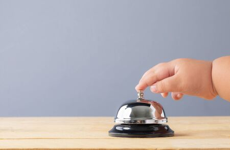 Hand s' child to press the bell service on wood table. Bell of service concept