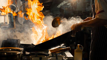 Chef stir fry cooking on wok with fire hard in kitchen