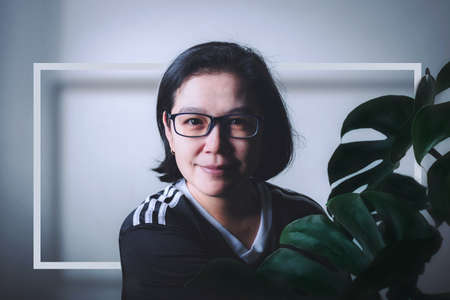 Portrait middle aged Asian woman is beautiful and Monstera leaf