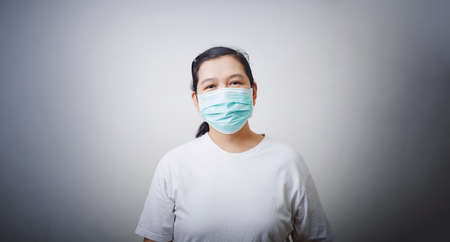 Asian Woman wears a facial mask on wall background
