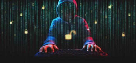 Hacker in hoodie dark theme. Hacker on screen with binary code Standard-Bild