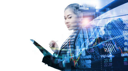 Business, people and technology concept - Smart Asian businesswoman with tablet pc computer over city buildings and graph stock market, double exposure effect