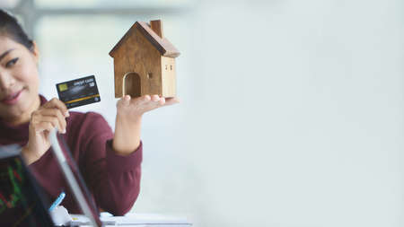 Hand of woman holding a toy house with copy space. Filing a home on credit