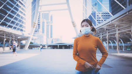 Young woman wearing protective face mask outdoors in city street.