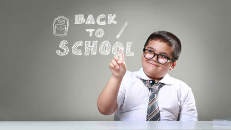 Happy smiling boy in glasses with concept back to school, The boy pointing back to school Standard-Bild