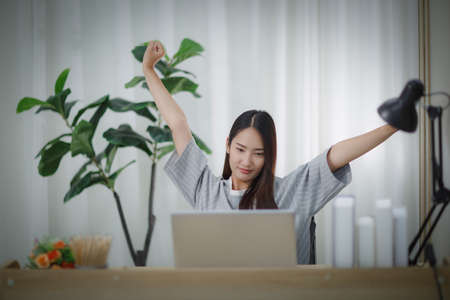 Asian woman sitting at home working in front of a laptop Arms spread out in exhaustion Standard-Bild