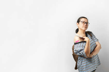 Asian woman ready for safe travel journey. Portrait of happy holding passport, smiling and showing arms after receiving  vaccine.  vaccination concept Standard-Bild