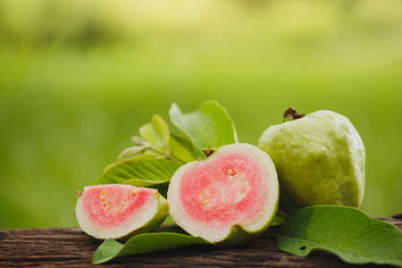 Guava sliced on wood table with green natural background