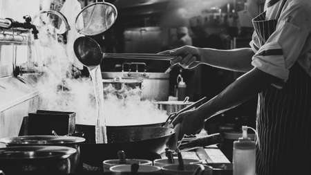 Chef stir fry the food in a frying pan, smoke and splatter the sauce in the kitchen.
