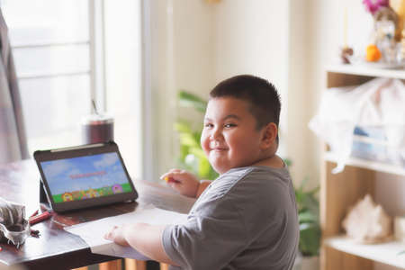 Cute Asian kid learning class study online  from tablet at home .Social distancing concept Standard-Bild