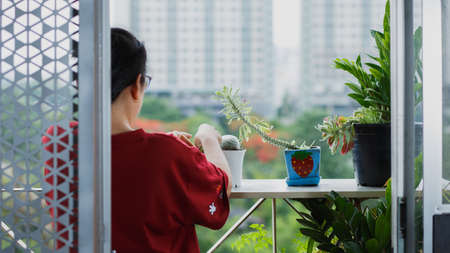 Women plant trees on the balcony of the condo room. A new normal of lifestyle for people after the epidemic