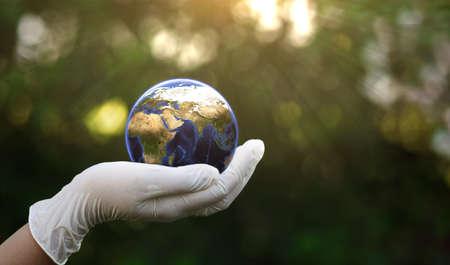 Hand in white glove holding Earth globe on bokeh background