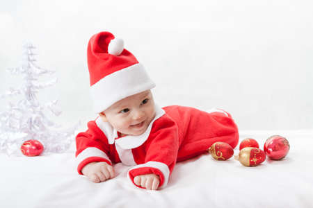 baby Santa Claus with a Christmas tree and toys photo