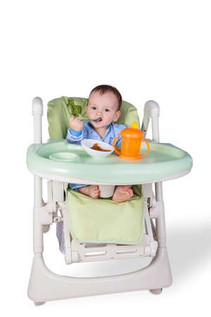 child is eating sitting at table, isolated over white Stock Photo - 17330388