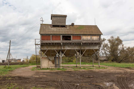 old grain dryer on the background of the autumn mud in Russia photo