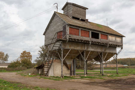 conveyors: old grain dryer on the background of the autumn mud in Russia
