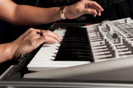 adjusting: Musician adjusting keyboard Stock Photo
