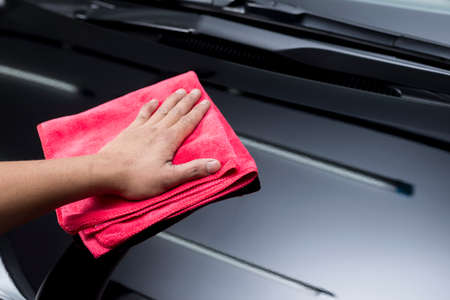 Car polishing series : Closeup of workers hand using red towel cleaning black car bonnet Фото со стока