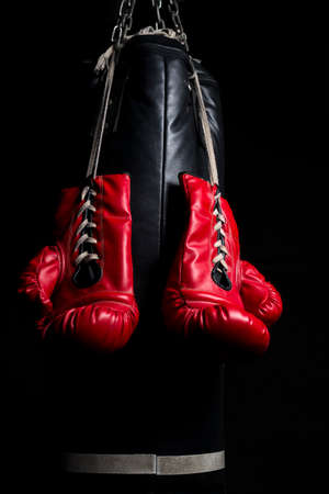 key punching: Red boxing gloves with low key lighting Stock Photo