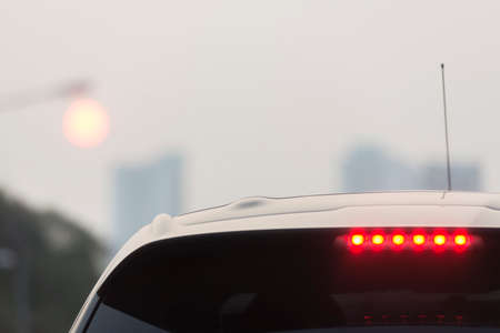 light red: Third brake lights of white car in foggy evening Stock Photo