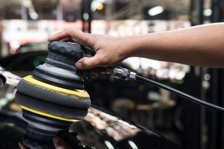 depilacion con cera: serie de pulido del coche: Primer de la mano del trabajador usando la herramienta de depilación capó del coche negro en el garaje