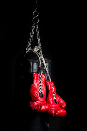 key punching: Pair of red boxing gloves with low key lighting Stock Photo