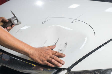 bonnet: Auto body repair series: Hands of worker checking dent on white car bonnet