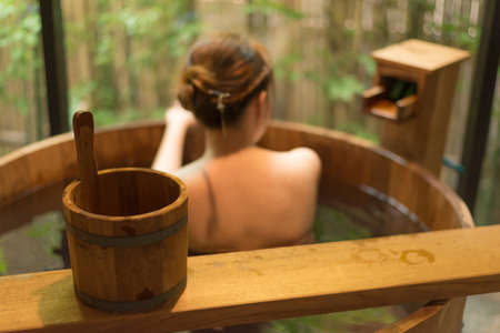 unrecognizable: Onsen series : Unrecognizable woman in wooden bathtub Stock Photo