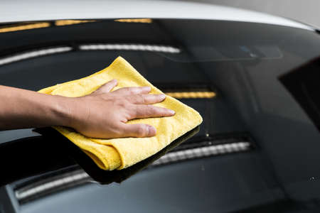 polisher: Car polishing series : Hand of worker using yellow towel wiping windshield