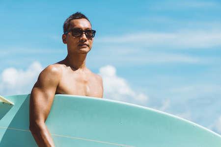 série Lifefstyle: homme asiatique tenant planche de surf sur la plage Banque d'images