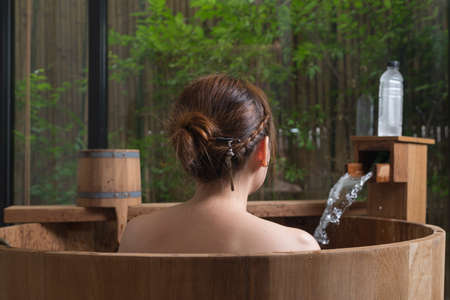 woman in bath: Onsen series : Unrecognizable woman in wooden bathtub Stock Photo