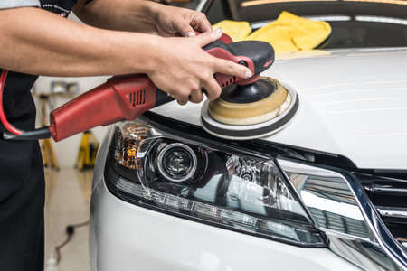 Car polishing series : Worker waxing white car Standard-Bild