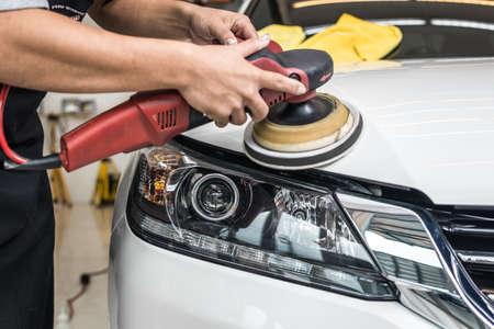 Car polishing series : Worker waxing white car Stock Photo
