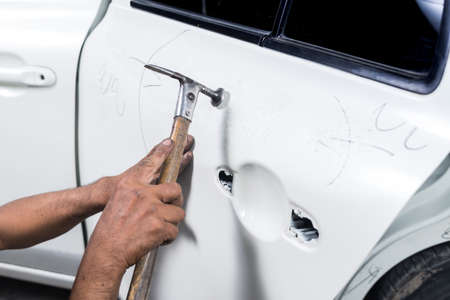 Auto body repair series : Worker repairs white car paint Фото со стока