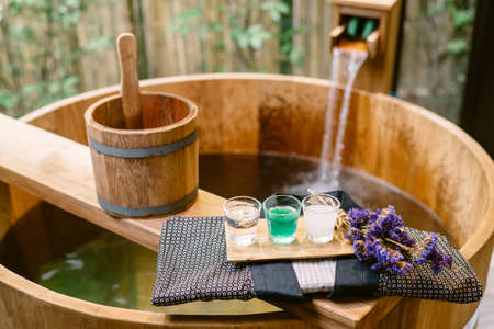 Onsen series : wooden bathtub with sample of mineral water Фото со стока - 51524118