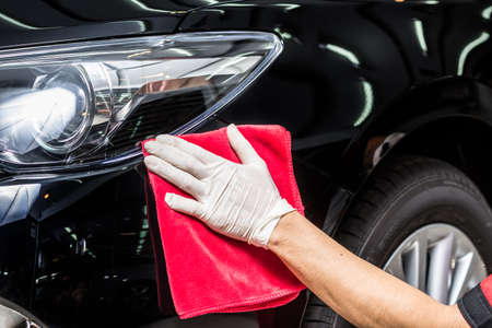 detailing: Car detailing series : Man using red towel wiping black car Stock Photo