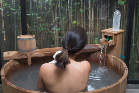 Onsen series : Unrecognizable woman in wooden bathtub Stock Photo