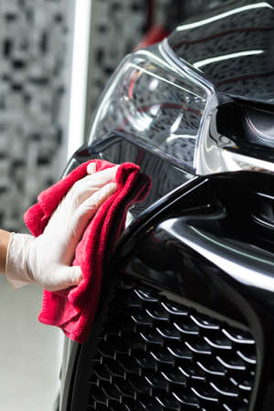 front bumper: Car polishing series : Man using red towel wiping black car front bumper