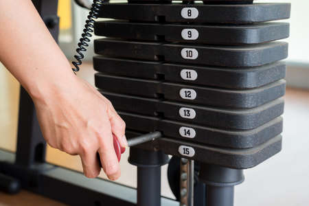weigh machine: Exercise series : Adjusting weigh on exercise machine Stock Photo