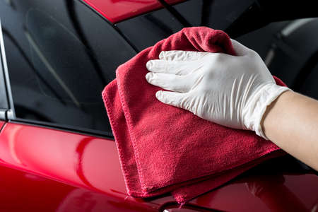 polishing: Car polishing series : Worker cleaning red car Stock Photo
