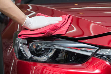 Car polishing series : Worker cleaning red car Archivio Fotografico