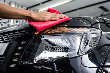 Car detailing series : Worker cleaning black car Standard-Bild