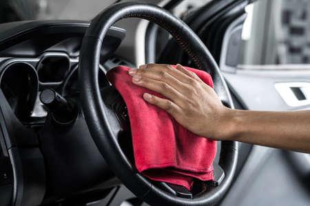Car detailing series : Worker cleaning steering wheel