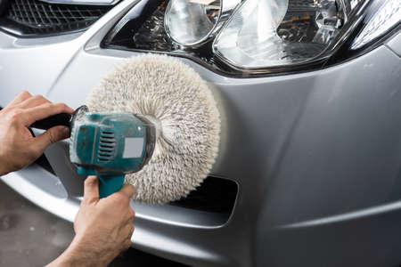 polisher: Car detailing series : Worker waxing grey car