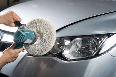 Car detailing series : Worker waxing grey car