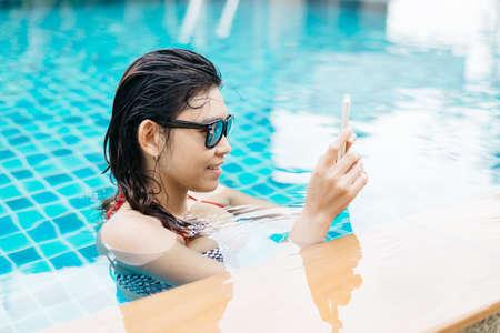 Swimming pool series : Using smart phone Stock Photo